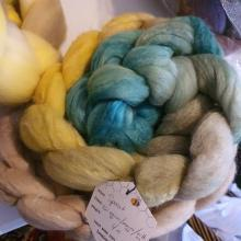 A braid of fiber in a gradient from tan through yellows, greens, and blues.